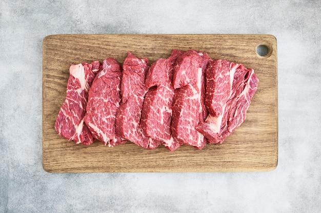 灰色の背景のコピースペース上面図の木製まな板に新鮮な生のビーフステーキ