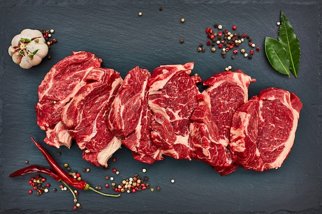 Fresh raw beef steaks with chilly pepper on black slate board