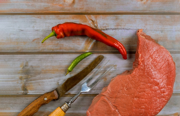 Fresh raw beef steaks with knife and red pepper on wooden background