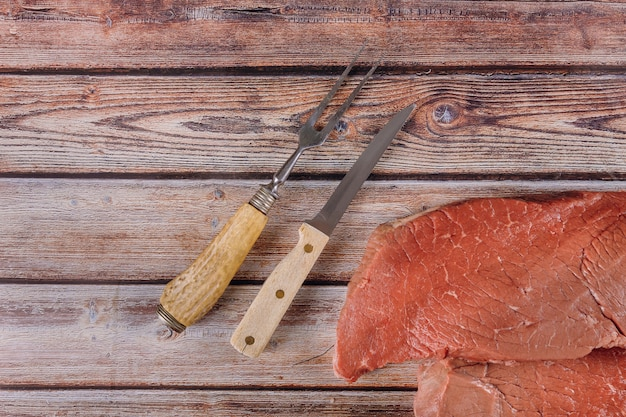 Fresh raw beef steaks with knife on wooden table