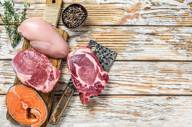 Стриплоин из свежей сырой говядины, филе куриной грудки, стейк из свинины и лосося. белый деревянный фон. вид сверху.