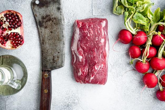 조미료와 로즈마리를 곁들인 신선한 생 쇠고기 안심, 자르지 않은 전체 조각 세트, 회색 돌 테이블, 평면도 평면