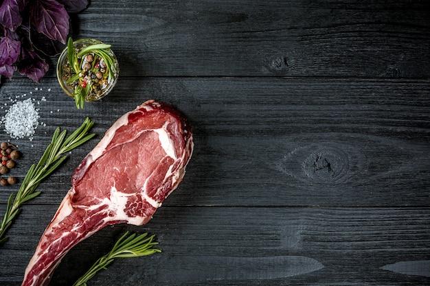 スパイス、新鮮なバジル、黒い木製の背景にローズマリーの小枝と新鮮な生の牛肉。上面図。スペースをコピーします。静物..乾燥熟成霜降り牛