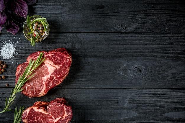 スパイス、新鮮なバジル、黒い木製の背景にローズマリーの小枝と新鮮な生の牛肉。上面図。スペースをコピーします。静物。