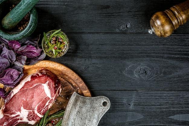 スパイス、新鮮なバジル、黒い木製の背景に肉用の斧とローズマリーの小枝と新鮮な生の牛肉。上面図。スペースをコピーします。静物..乾燥熟成霜降り牛