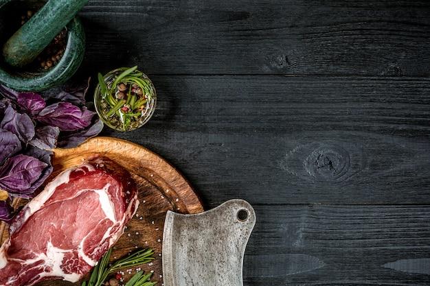 スパイス、新鮮なバジル、黒い木製の背景に肉用の斧とローズマリーの小枝と新鮮な生の牛肉。上面図。スペースをコピーします。静物。