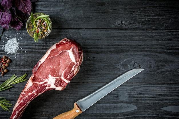スパイス、新鮮なバジル、黒い木製の背景に木製の柄が付いたナイフでローズマリーの小枝と新鮮な生の牛肉。上面図。スペースをコピーします。静物。