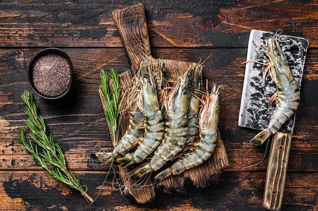 Fresh raw black tiger prawns, shrimps on a cutting board.