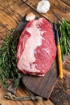 신선한 생 양지머리 쇠고기 고기는 허브와 함께 나무 판자에 잘립니다. 나무 배경입니다. 평면도.