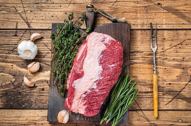 Свежие сырые грудинки говядины премьер вырезать на деревянной доске с зеленью. деревянный