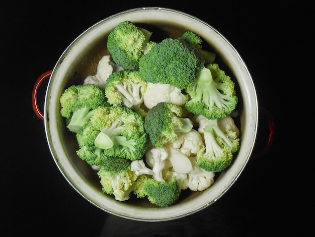 Fresh raw broccoliand cauliflower in a metal pan on a dark background. broccoli florets ready for cooking.