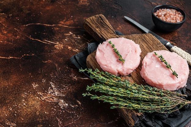 닭고기와 허브를 곁들인 칠면조 고기로 만든 신선한 생 버거 패티 커틀릿. 어두운 배경입니다. 평면도. 공간을 복사합니다.