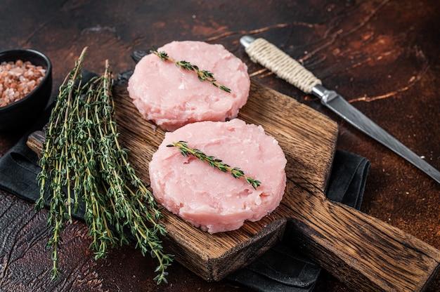 닭고기와 허브를 곁들인 칠면조 고기로 만든 신선한 생 버거 패티 커틀릿. 어두운 배경입니다. 평면도.