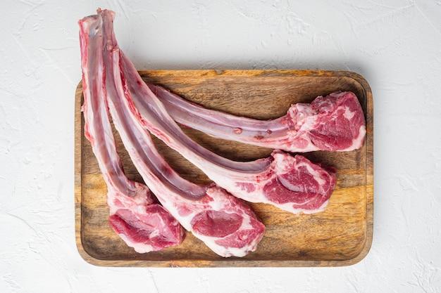 Набор свежих сырых мясных котлет из баранины, на белом каменном столе, плоский вид сверху