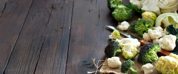 Fresh raw cauliflower and broccoli on an old wooden table top view