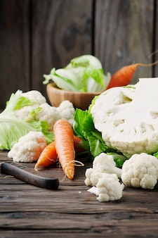 Fresh raw cauliflower and carrot on the wooden table