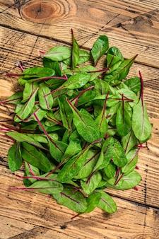 Свежие сырые листья мангольда, мангольд, швейцарский мангольд на деревянном кухонном столе. деревянный фон. вид сверху.