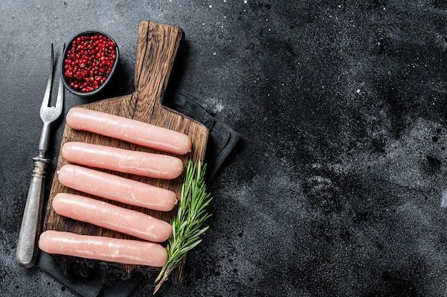 Свежие сырые сосиски из курицы и мяса индейки на деревянной доске с розмарином