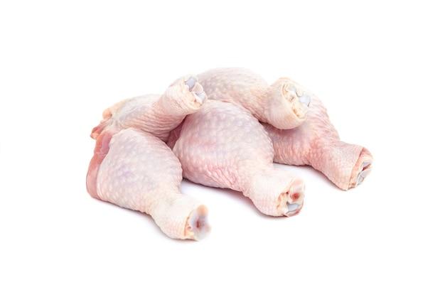 Свежие сырые куриные голени на белом фоне