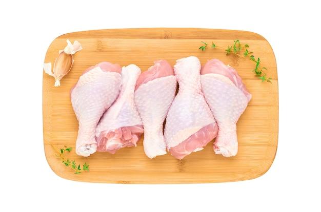 Свежие сырые куриные голени на деревянной доске