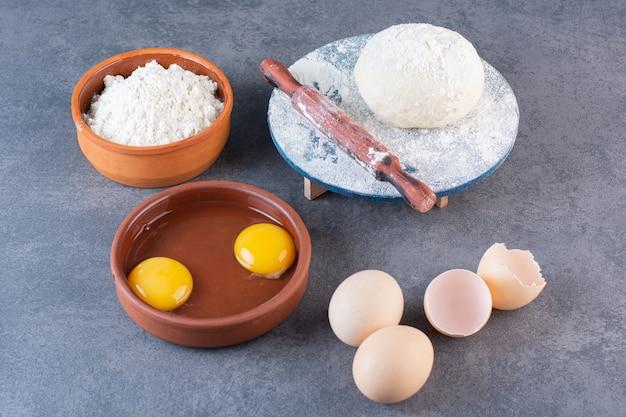 밀가루와 신선한 생 계란은 돌 테이블에 배치합니다.