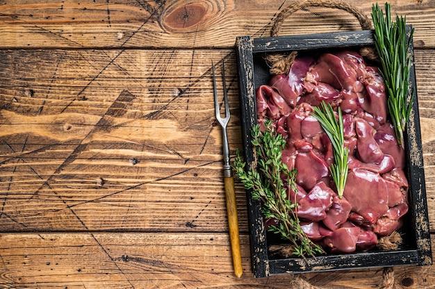 신선한 생 닭 간은 나무 쟁반에 고기를 담습니다. 나무 배경입니다. 평면도. 공간을 복사합니다.