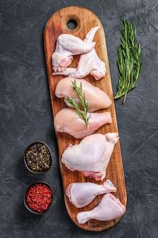 신선한 생 닭고기와 닭고기 부분. 검정색 배경. 평면도.