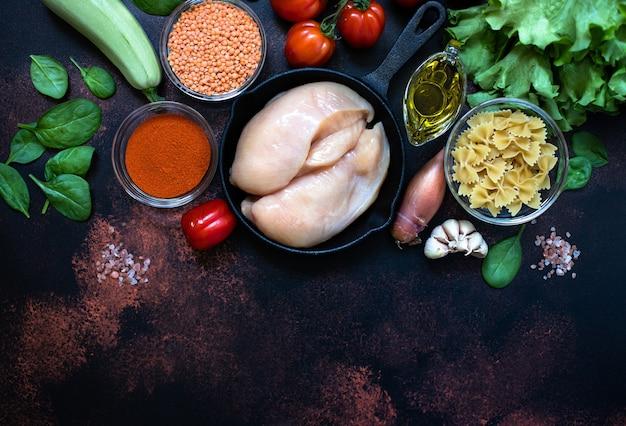 신선한 생 닭 고기, 어두운 소박한 배경에 건강 식품 재료로 둘러싸인 냄비에 치킨 필렛. 평면도, 복사 공간