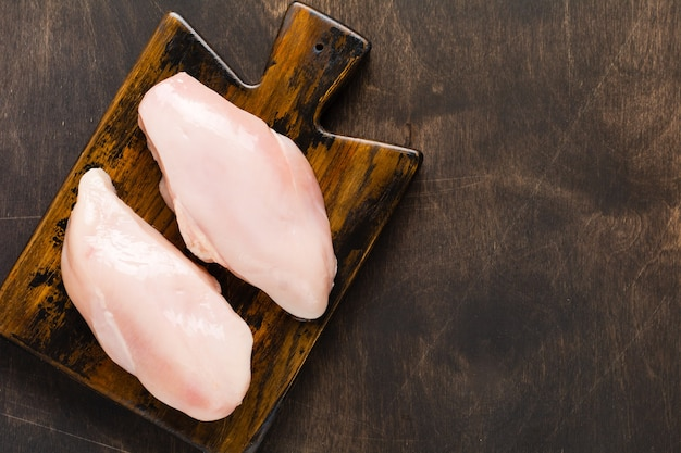 Fresh raw chicken meat fillet with salt, pepper, onion and butter on a wooden board on a dark wooden rustic background. top view.