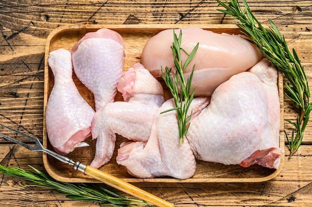 Свежее сырое куриное мясо, крылышки, грудка, бедра и голени на деревянном подносе. деревянный фон. вид сверху.