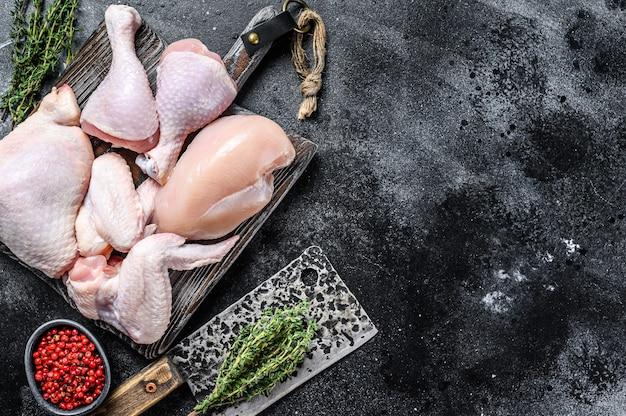Свежее сырое куриное мясо, крылышки, грудка, бедро и голени. вид сверху.