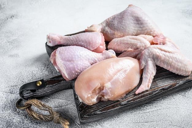 Свежее сырое куриное мясо, крылышки, грудка, бедра и голени. белый фон. вид сверху.