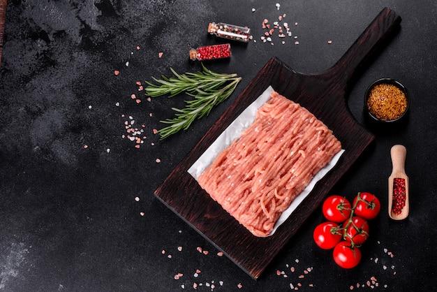 暗い木製のまな板に新鮮な生の鶏ミンチ