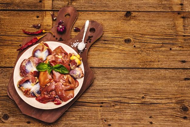 Свежие сырые куриные субпродукты: сердце, печень, желудок с сухими специями, морская соль, перец чили на деревянном столе