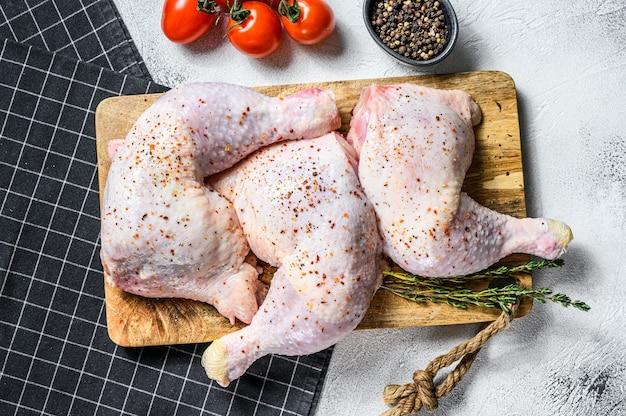 신선한 생 닭 허벅지, 향신료와 함께 커팅 보드에 다리, 요리