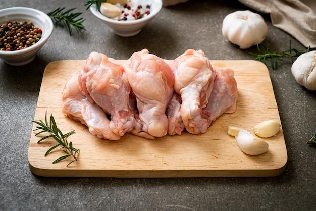 목 판에 신선한 생 닭 날개 (드럼 또는 드럼 스틱)