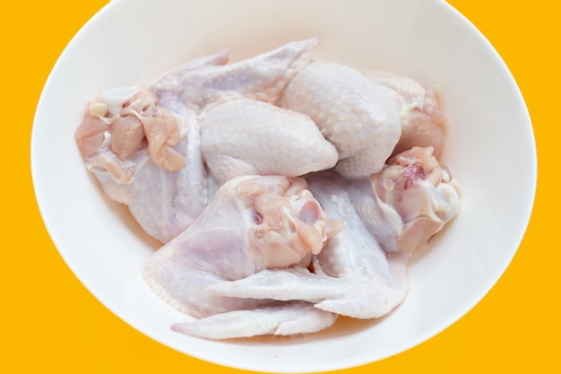 Свежие сырые куриные крылышки в белой миске на желтом фоне.
