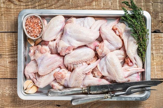 신선한 생 닭 날개 허브와 함께 부엌 쟁반에 가금류 고기.