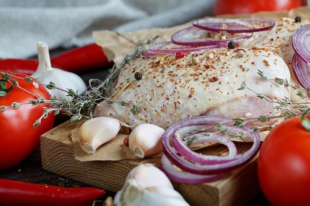 Свежая сырая курица с зеленью, чесноком, луком, помидорами и перцем чили