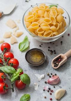 パルメザンチーズとトマト、油とニンニクとバジルの明るい背景のガラスのボウルに新鮮な生の古典的なコンキリエパスタ。上面図