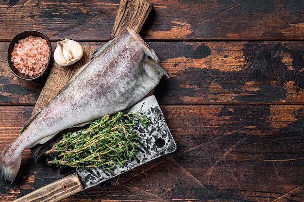 Свежая сырая треска или треска на деревянной доске с тесаком