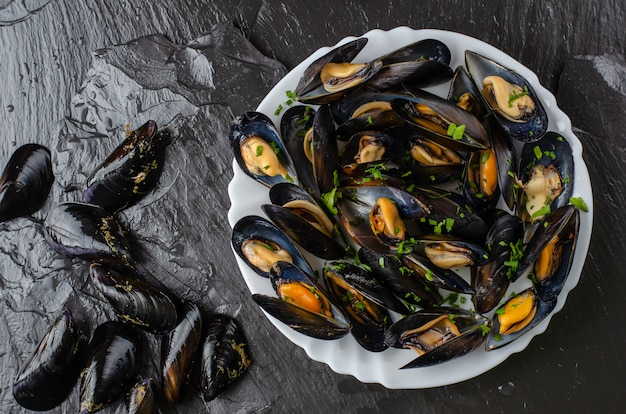 Fresh raw and cooked mussels on black slate stone background