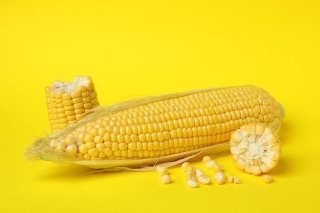 黄色の背景に新鮮な生のトウモロコシ、クローズアップ