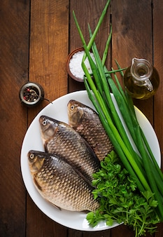 Fresh raw crucian on a wooden with herbs.