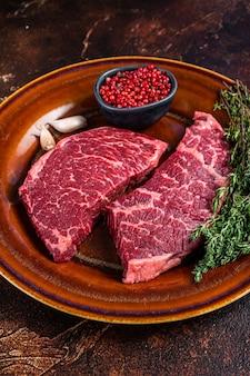 백리향이 있는 소박한 접시에 신선한 생 덴버 또는 톱 블레이드 고기 스테이크. 어두운 배경입니다. 평면도.