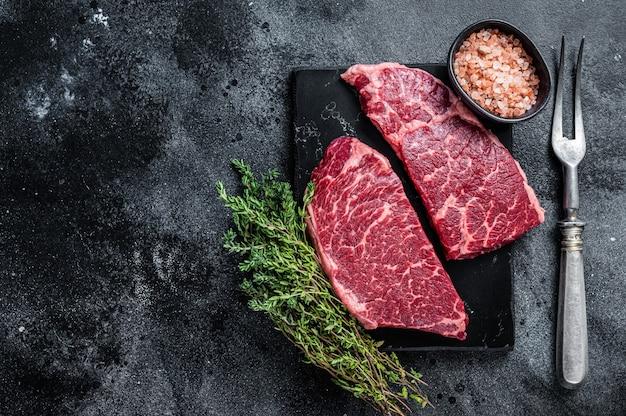 신선한 생 덴버 스테이크 허브와 함께 대리석 쇠고기 고기입니다. 검은 배경. 평면도. 공간을 복사합니다.