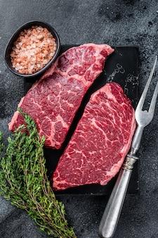 新鮮な生のデンバーステーキ霜降り肉とハーブ。黒の背景。上面図。