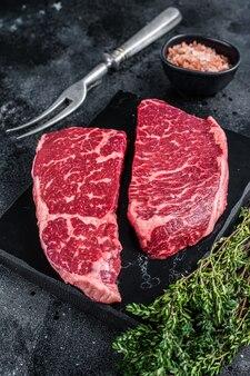 Свежий сырой стейк из денвера мясо из мраморной говядины с зеленью.