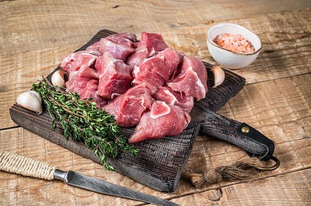 Свежее сырое нарезанное кубиками мясо новичков свинины со специями на деревянной доске мясника. деревянный стол. вид сверху.