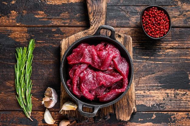 Свежие сырые нарезанные кубиками ломтики филе красной говядины в чугунной сковороде